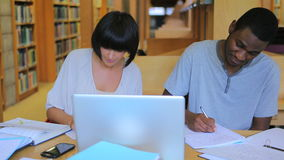 People working on assignments in the library stock video footage