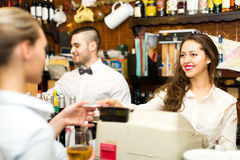 People working in a bar. Waitress is taking a check from a cashier while handsome bartender is mixing drinks in background Stock Images