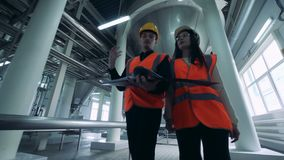 Man and woman walking in a brewery room with containers, close up. stock footage