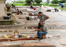 People working in the carpet of sand Stock Photo