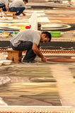 People working in the carpet of sand Stock Photography