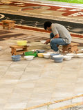 People working in the carpet of sand Stock Images
