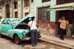 People working on a classic car in Havana, Cuba. Classic old car on streets of Havana, Cuba Stock Photo