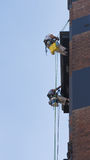 People working climbers. Two unrecognizable workers climber, with special equipment and buckets down on the wire ropes on the wall of a brick building against a Royalty Free Stock Photography