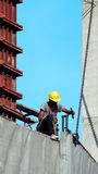 People working on construction site with yellow helmet. And safty rope equipment and covering the building with grey color vinyl and blue sky Royalty Free Stock Photos
