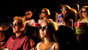 A group of excited young attractive happy male female friends enjoying 3d 4d action movie theater cinema eating popcorn
