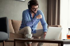 People working at home- man uses a laptop to listen to music and