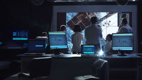 People working in mission control center. Back view of people working and managing flight in mission control center. Elements of this image furnished by NASA