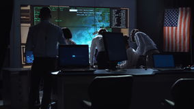 People working in mission control center. Back view of people working and managing flight in mission control center. Elements of this image furnished by NASA stock video