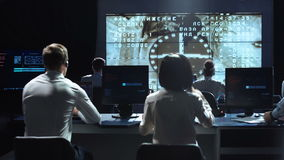 People working in mission control center. Elements of this image furnished by NASA.