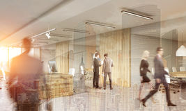 People working in modern wooden office with cityscape. Rear view of people standing and going in modern office decorated with wood. Concept of large corporation Stock Photos