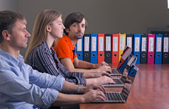 People working at office on computers sitting in row Royalty Free Stock Photography