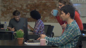 People working office desk drinking coffee talking discussing looking computer screen stock footage