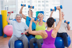 People working out with dumbbells at fitness class. Female trainer with class working out with dumbbells at fitness class Stock Photo