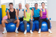 People working out on exercise balls at gym class Royalty Free Stock Images