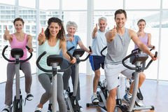 People working out at spinning class while gesturing thumbs up Stock Image