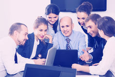 People working productively on business project together. Happy russian people working productively on business project together in office Royalty Free Stock Photos