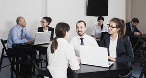 People working productively on business project together. Happy spanish people working productively on business project together in office Stock Photography
