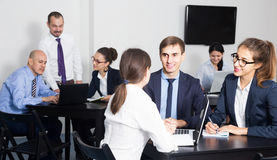 People working productively on business project together. Positive russian people working productively on business project together in office Royalty Free Stock Images