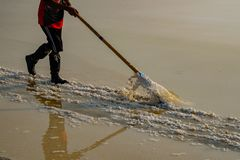 People working in sea salt field in Thailand stock photo