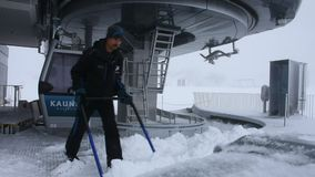 People working sweep snow at cable car station at top of mountain. TYROL, AUSTRIA - SEPTEMBER 3 : Karlesjochbahn cable car transport station and people working stock video footage