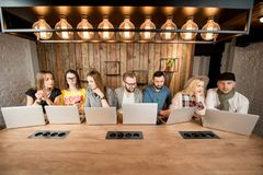 People working together with laptops. Young coworkers working together with laptops sitting in a row at the wooden table in the modern workspace royalty free stock image