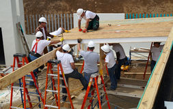 People working in wood rooftop for a medic centre Royalty Free Stock Images
