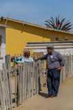 People of the World - African senior couple. Senior African couple talking to each other standing against a wooden fence, Swakopmund, Namibia Stock Photos