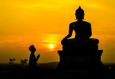 People worship Buddha, Buddha statue on sunset sky background Royalty Free Stock Image