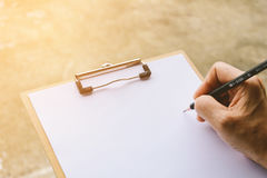 People are writing a message on it paper on clipboard Royalty Free Stock Images
