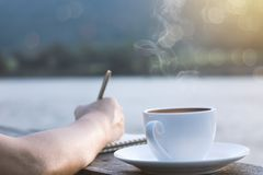 People writing and planning work on wooden balcony and cup of hot coffee for brackfast near river and mountain. Background stock photos