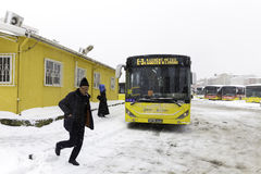 People and yellow public bus on a snowy winter day Royalty Free Stock Image