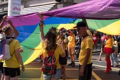 People in yellow t-shirts standing under giant LGBT rainbow flag during the Gay Pride Parade 2018. London UK, July 2018. People in yellow t-shirts standing stock images