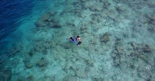 People young boys girls snorkeling over coral reef with drone aerial flying view in crystal clear aqua blue. Many people young boys girls snorkeling over coral stock photography