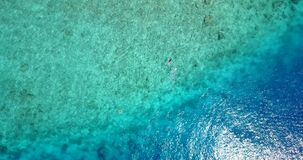 2 people young couple snorkeling over coral reef with drone aerial flying view in crystal clear aqua blue. Two 2 people young couple snorkeling over coral reef royalty free stock images