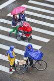 People on zebra crossing with umbrella and rainwear, Shanghai, China. SHANGHAI–MAY 4, 2014. People with umbrella and rainwear on wet zebra path. Shanghai stock image