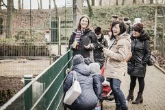 People at a zoo. Group of laughing people feeding animals at the Alsdorfer zoo in Alsdorf, Germany Stock Photography