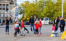 People in Zurich watching a street artist making soap bubbles. Zurich, Switzerland - 1 October, 2017: people on General Guisan quay watching a street artist Royalty Free Stock Images