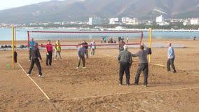 Peopleelderly che gioca nella pallavolo sulla spiaggia stock footage