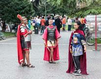 Peoples are dressed as legionaries stand  near Arena in Verona. Verona, Italy, September 27, 2015 : Two men and one woman dressed in the form of Roman Royalty Free Stock Photos