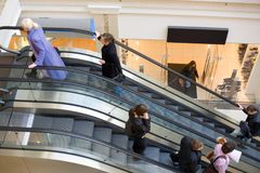 Peoples on escalators in a mall. Motion blur Stock Photos