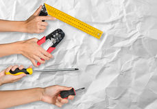 Peoples hands holding tools. Peoples hands holding different tools on crumpled paper background royalty free stock image