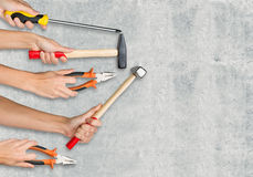 Peoples hands holding tools. Peoples hands holding different tools on grey background royalty free stock images