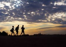 Peoples in silhouette walking on the background of sunset and cl. Oudy sky. Evening time Stock Photography