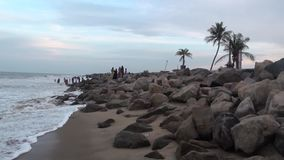 Peoples stands on rocks near sea at sunny day stock video