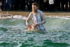 Peopls游泳在突然显现(圣洁洗礼)期间的冰冷的水黑海中在正统传统 免版税库存图片