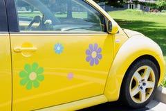 Peoria, IL/USA - insect van VW van 06-13-2018 het Heldere gele met gelukkige bloemoverdrukplaatjes stock foto