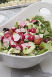 Peparation of a Salad with greens, radishes, cucmbers, olives, t. Preparation of a Salad made with greens, lettuce, radishes, cucmbers, olives, tomatoes in a Stock Photo