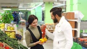 Pepe d'acquisto e pomodori delle coppie felici alla drogheria o al supermercato archivi video