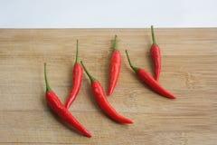 Pepe di peperoncino rosso rosso su una scheda di taglio Fotografie Stock Libere da Diritti